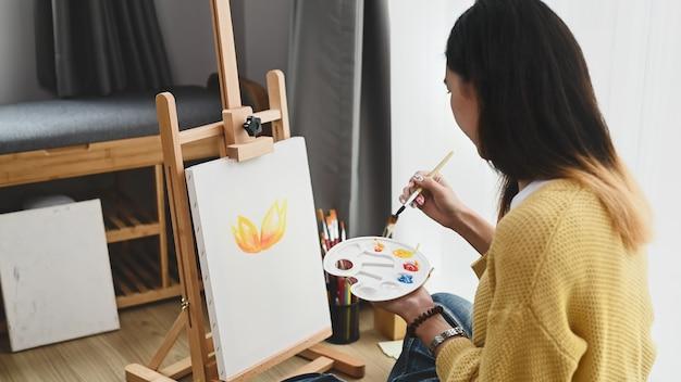 若い女性アーティストが手にパレットを持ってスタジオで絵を描いています