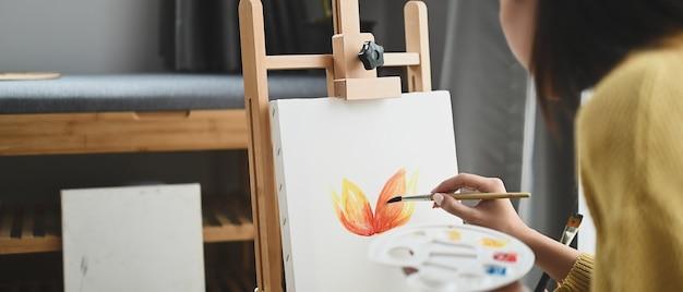 若い女性アーティストがワークスペースでアートワークを描いています