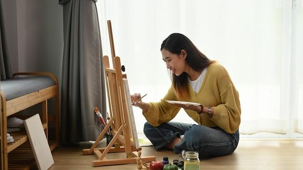若い女性アーティストが彼女のワークショップでキャンバスに絵を描き、床に座っています