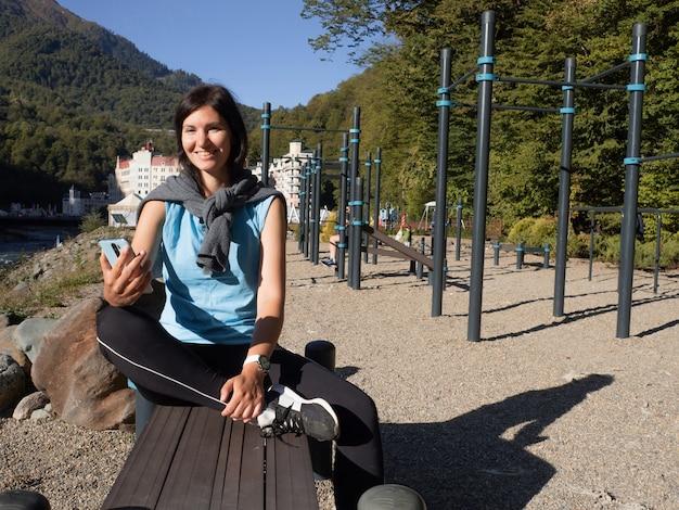 Молодая спортсменка сидит на открытом спортивном поле, отдыхает после тренировки. счастливая брюнетка использует смарт-часы и приложения для смартфонов, чтобы отслеживать спортивную статистику. активный отдых на открытом воздухе.