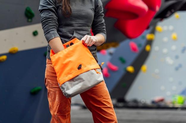 若い女性の登山家がクライミングウォールを登る準備をしています。