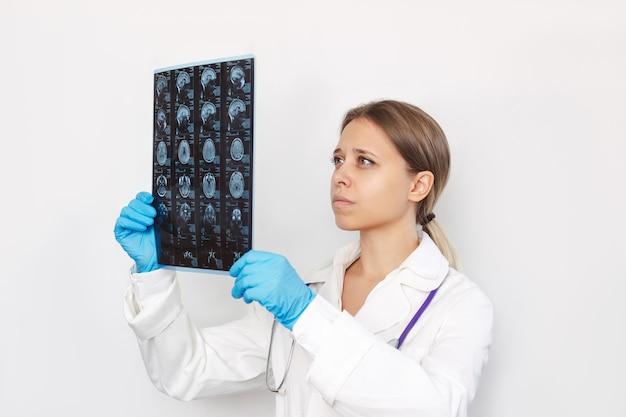흰색 배경에 격리된 환자의 머리와 뇌의 mri 스캔을 검사하는 젊은 여성 의사