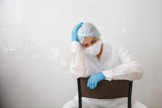 방호복 모자와 장갑을 낀 젊은 여의사가 내 의자에 지쳐 앉아 있다...