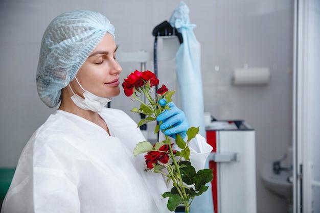 흰색 보호복 모자와 장갑을 낀 젊은 여성 의사가 그녀에게 선물된 빨간 장미를 들고 있다