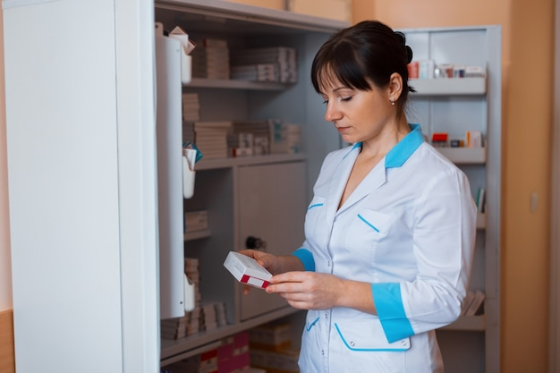 Молодая женщина-врач в белой форме стоит в комнате для медперсонала возле шкафа с таблетками и проверяет срок годности лекарств.