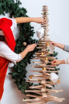 Молодая женщина в шляпе красного карлика украшает стилизованную елку масками для лица, коронавирусом и рождественской концепцией