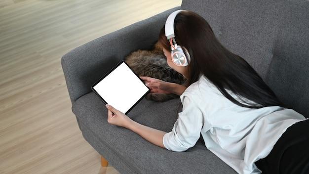 Молодая женщина лежит на диване и использует планшет во время прослушивания музыки в беспроводных наушниках.