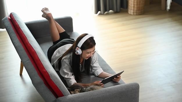 若い女性が自宅のソファに横になってワイヤレスヘッドホンで音楽を聴きながらタブレットを使用しています。