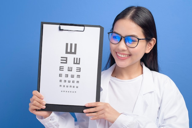 青い壁の上に視力検査表を保持している眼鏡をかけた若い女性の眼科医