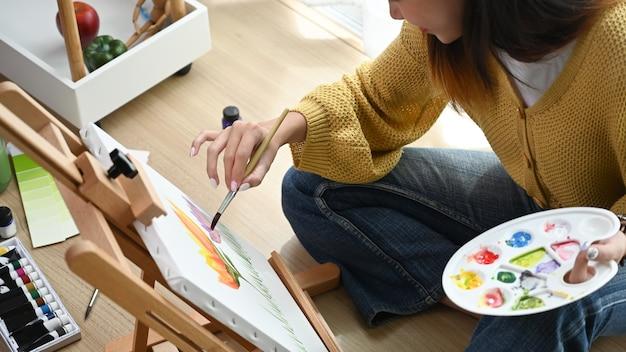 若い女性画家がスタジオでアート作品を作成しています