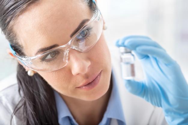 若い女性科学者は、保護メガネと衛生手袋を使用して化学物質を研究しています。