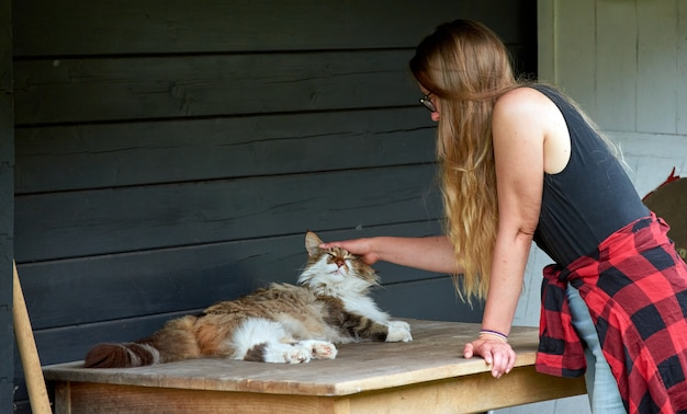 Молодая самка гладит милую кошку