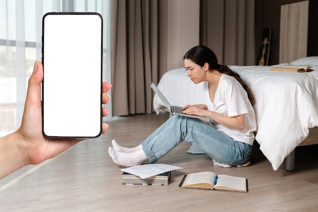若い女子学生が床に座って、ラップトップで熱心に働いています。手は左側のスマートフォンを持っています。モックアップ。オンラインコースと教育の概念。