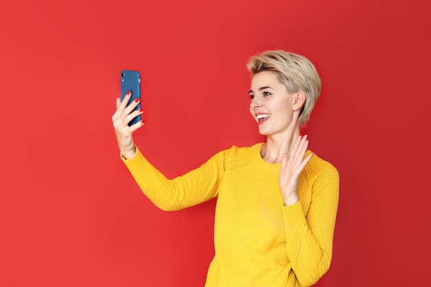 젊은 여성 동영상 블로거가 스마트 폰의 화상 통화를 통해 카메라를 향해 인사하며 소통합니다.