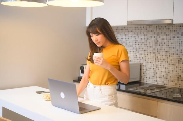 彼女のラップトップで働いて、一杯のコーヒー、ライフスタイルとビジネスコンセプトを持っている若い女性