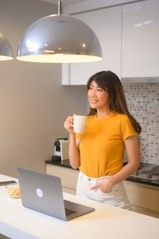 노트북으로 작업하고 커피 한 잔, 라이프 스타일 및 비즈니스 개념을 가진 젊은 여성
