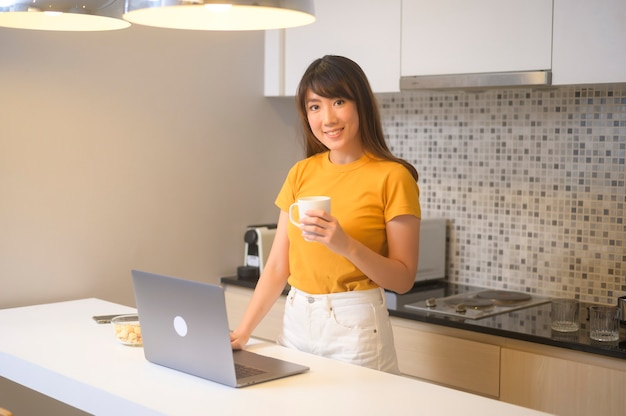 Молодая женщина, работающая со своим ноутбуком и выпивающая чашку кофе, образ жизни и бизнес-концепцию