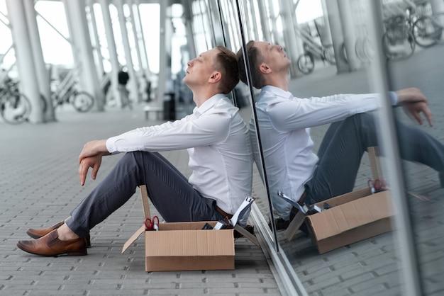 若い解雇されたサラリーマンが彼のオフィスの下に座っています。彼の隣には文房具があります。男はストレスを感じています。