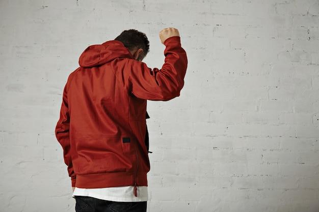 Молодой подтянутый мужчина-модель в спортивной куртке кирпично-красного цвета держит кулак в воздухе, портрет со спины изолирован на белом