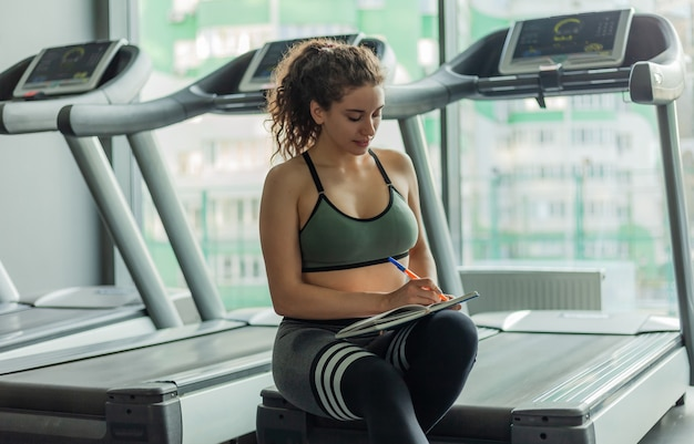 젊은 맞는 여자는 체육관에서 훈련의 추가 진행을 위해 훈련 책에 정보를 씁니다. 건강한 라이프 스타일 개념. 운동 계획