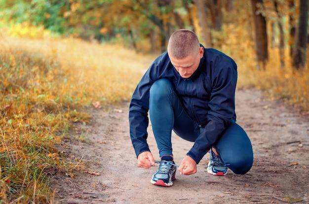 검은 스포츠 레깅스와 스니커즈의 젊은 피트니스 운동 선수는 노란색 가을 숲의 경로에 끈을 묶습니다.