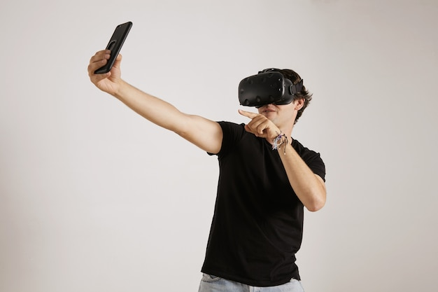 흰 벽에 스마트 폰으로 셀카를 위해 포즈를 취하는 검은 티셔츠와 vr 헤드셋의 젊은 게이머
