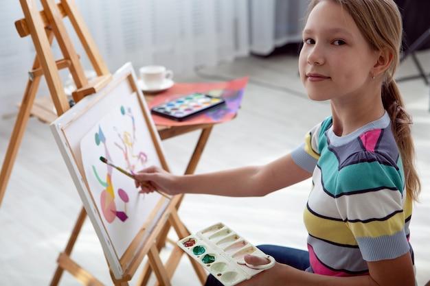 Юная одаренная девушка-художник пишет картину, сидя за мольбертом.