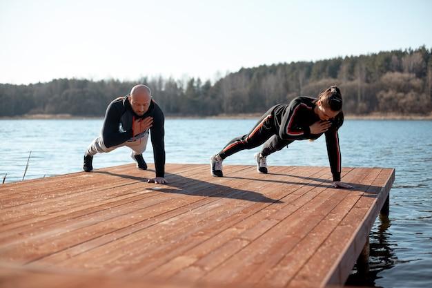 Юная девушка и мужчина в спортивной одежде занимаются спортом на пристани у озера. спорт, здоровье, активные хобби