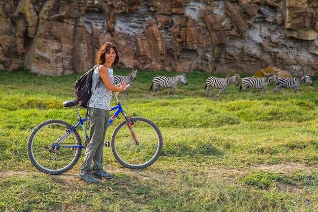Молодая девушка едет на велосипеде вместе с зебрами в национальном парке найваша адские ворота, полном животных. прогулка по кении или сафари на велосипеде