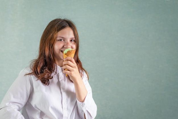Молодая девушка кусает фисташковое мороженое в вафельном стаканчике.
