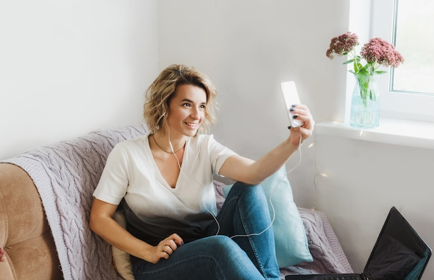Молодая девушка-блогер ведет онлайн-трансляцию, общается со своими подписчиками, сидя дома
