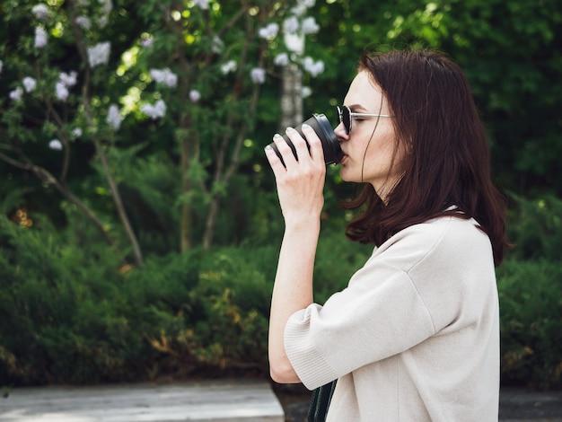黒い眼鏡をかけた茶色の髪の少女が、路上で使い捨てのコップからコーヒーを飲みます。休憩中、公園で女性が喜んでお茶を飲む。