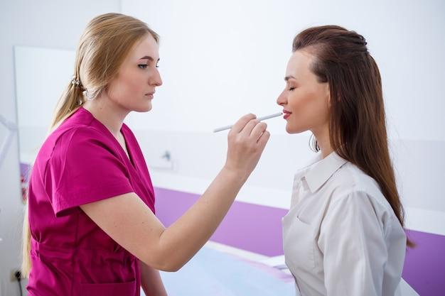 한 어린 소녀가 전문 미용사인 자격을 갖춘 의사와 약속을 잡기 위해 진료소에 왔습니다. 의사는 환자의 얼굴에 있는 피부 상태를 검사합니다