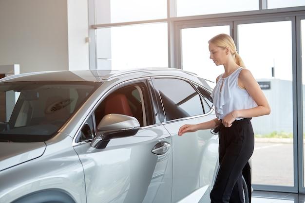 若い女の子がディーラーで新しい高級車を選ぶ