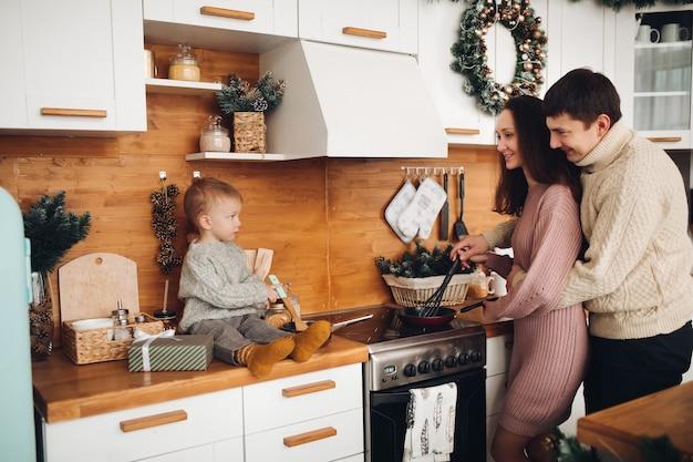 Молодая девушка обнимается с мужем и готовит ужин рядом с их ребенком