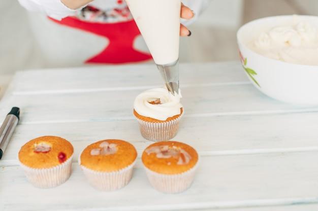 若い女の子がカップケーキをクリームで飾ります。