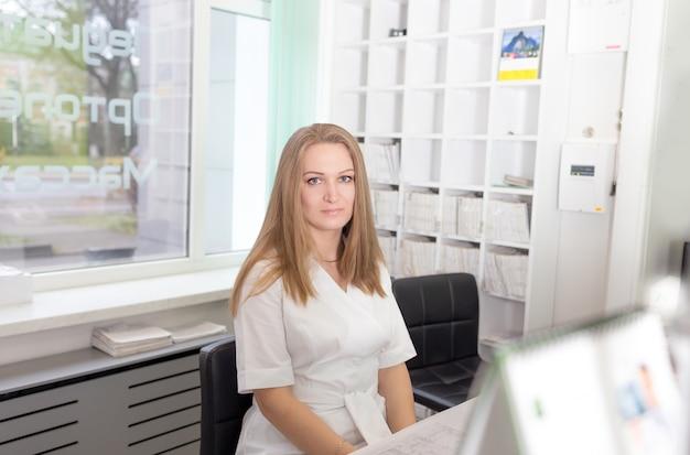 흰 코트를 입은 어린 소녀 의사가 대기실에 앉아있다.