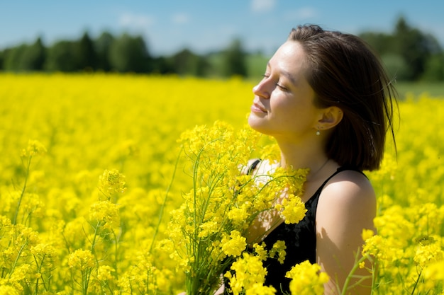 Молодая девушка мечтает о желтом поле рапса на голубом небе летом