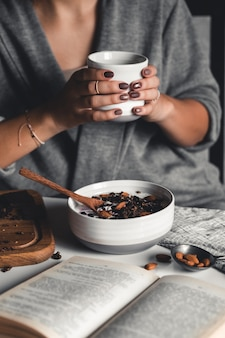 어린 소녀가 모닝 커피를 마시고 건강한 아침 식사를하고 책을 읽습니다. 아침 루틴. 세련된 매니큐어. 올바른 습관. 그의 손에 컵을 들고
