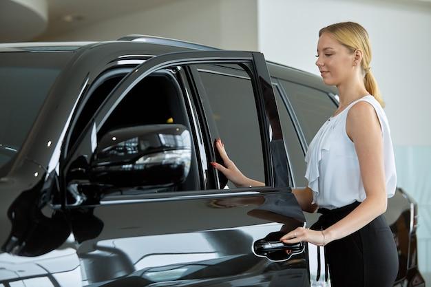 若い女の子が自動車販売店で購入する前に車を調べます