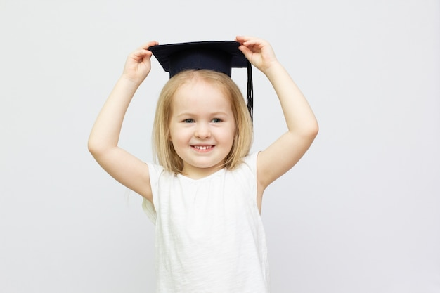 若い女の子は、白い孤立した背景にタッセル付きの卒業式の黒い帽子をかぶっています。学校や教育のコンセプトに使用してください。