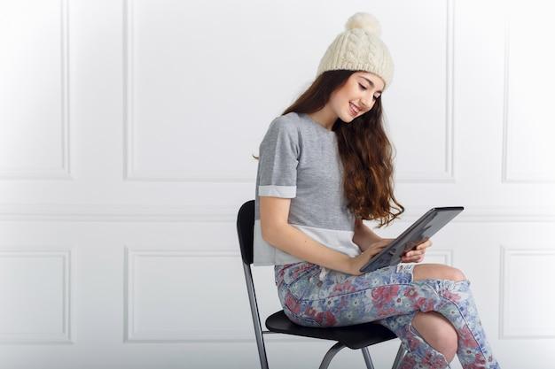 Молодая девушка держит планшет в руках с сенсорным экраном, сидя на высоком стуле, изолированном на белой стене