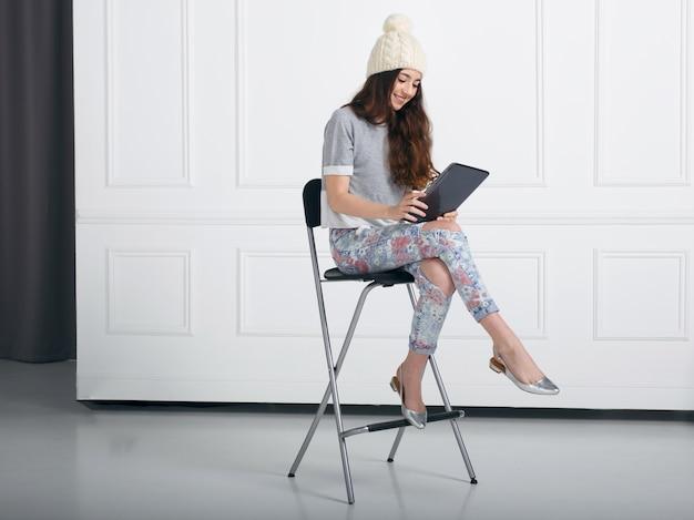 Молодая девушка держит планшет в руках с сенсорным экраном, сидя на высоком стуле