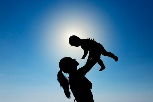 若い女の子は太陽に対して彼女の腕の中で子供を抱きます。シルエット写真。高品質の写真