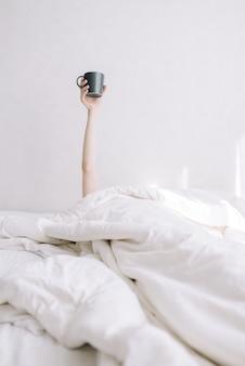 어린 소녀가 침대에서 뻗은 손에 커피 한 잔을 보유하고 있습니다.