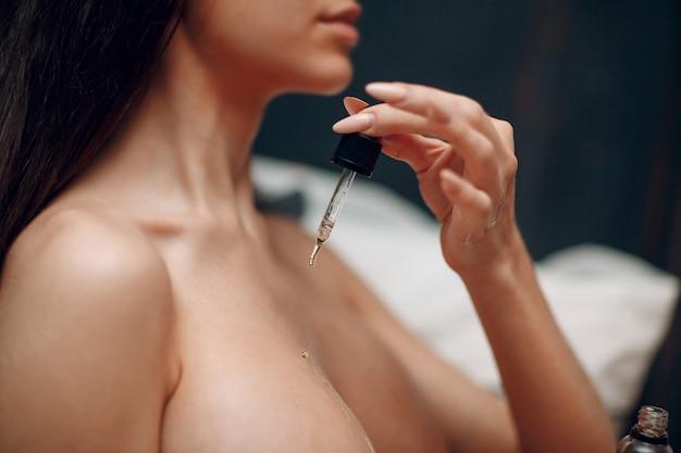 若い女の子は、化粧品の油でピペットを保持しています。スキンケアのコンセプトです。