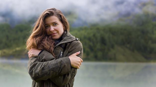 山で朝の寒さから若い女の子が肩を抱きしめる