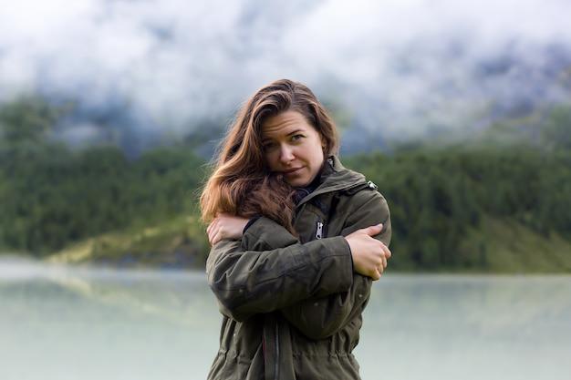 Молодая девушка обнимает себя за плечи от холода утром в горах