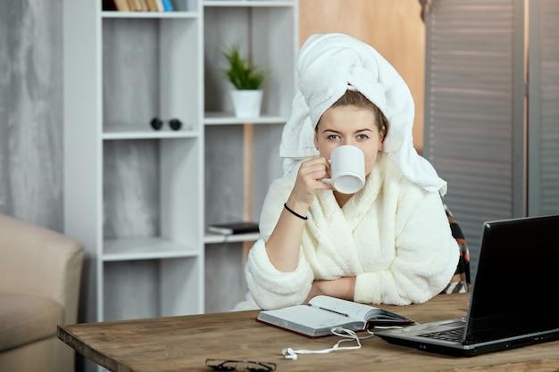 Молодая девушка в халате и с полотенцем на голове сидит с чашкой чая в руках.
