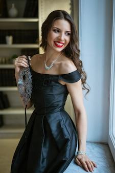 首にネックレスが付いた美しい黒のドレスの少女は、カーニバルのマスクを保持し、窓辺の窓辺に座っています。